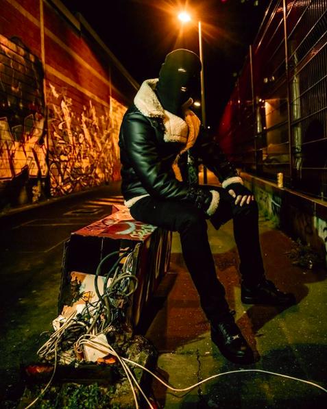 Malaa assis dans la rue lors d'un shooting avec Tokimur